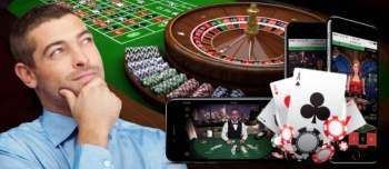 Man vid roulettbord, mobiler, spelkort och spelmarker
